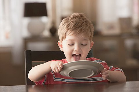 Five-year-old redheaded and adorable boy in a red T-shirt sits at the table and licks a white plate clean with his tongue, which he holds with both hands