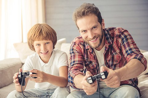 Cool full-bearded dad in a lumberjack shirt playing console games with his blond, enthusiastic six-year-old son
