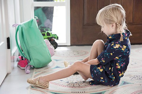 Six-year-old blonde girl with plaits and blue flower summer dress sits on carpet in the house entrance and puts on her sandals conscientiously