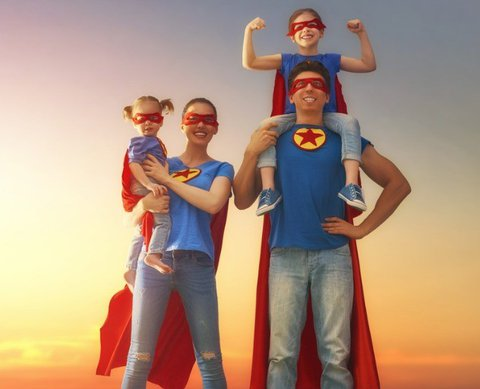 Super hero family, father, mother and two kids standing in front of blue sky with evening dawn