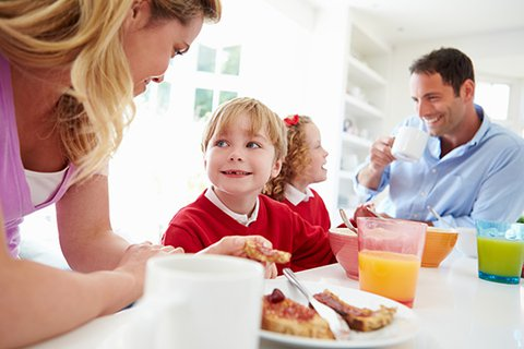 Relaxed family breakfast, blonde mum talks to twin son while dad talks and smiles to twin daughter and drinks coffee