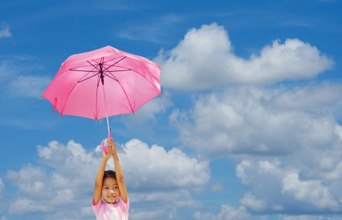 Mary Poppins girl with umbrella in front of blue sky