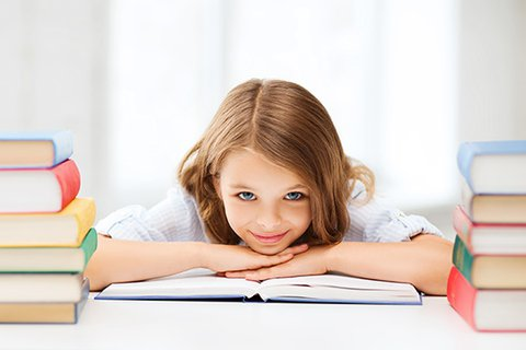 Eight-year-old girl with long, light brown hair lies relaxed and smiling with her chin on an open textbook, on a neat, structured desk