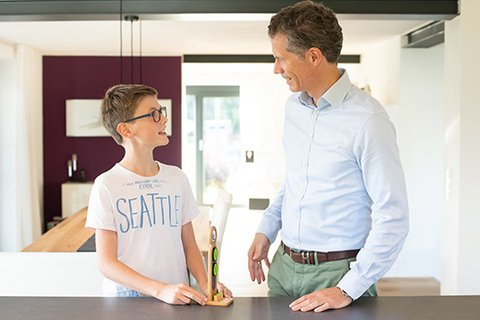 Father gives his twelve year old son sincere feedback, both standing on the kitchen block, with great pride in the boy's eyes and upright posture on both sides