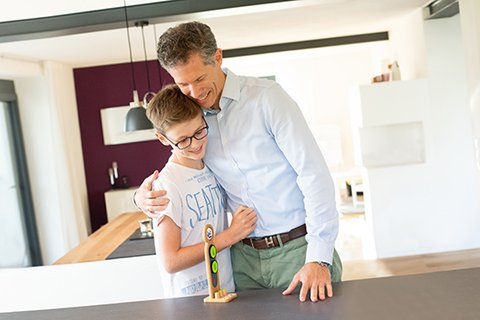 Father praises twelve-year-old blonde son and proudly embraces him with a view of his taskboard figure, standing at the kitchen unit