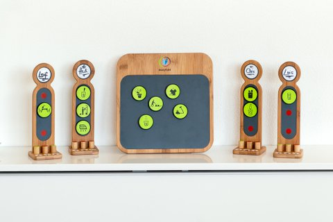 Taskboard Set: Agile method board set to distribute workload witin a group in a selforganising way. Bamboo board with antracite metal plate inlay and four bamboo figures next to it, standing on white sideboard