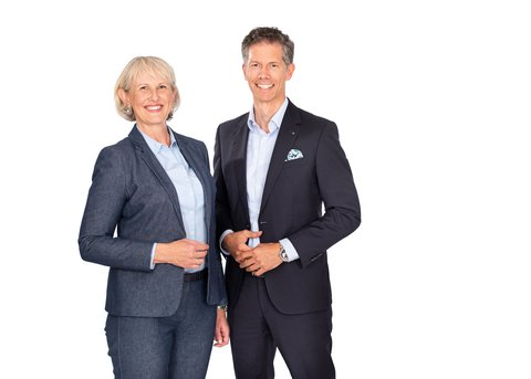 easyfaM founder Heidi Eineder and founder Christian Eineder stand smiling next to each other, both in a blue suit