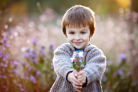 Six-year-old blond cute smiling boy with a grey knitted vest standing in front of a flower meadow, stretching out a bouquet of flowers he has picked himself