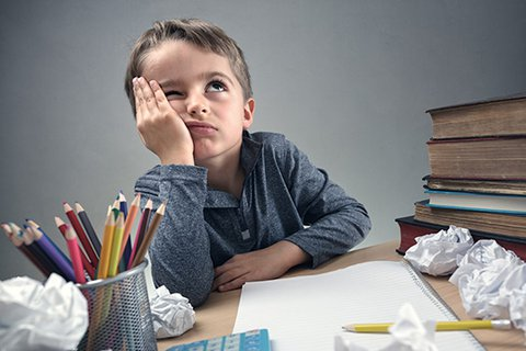 Desperate seven-year-old boy with his head resting, looking to the ceiling, at a chaotic desk between balls of paper, books and pens.